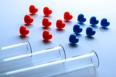 Abriveatura IVF de corazones rojos y azules y de tres tubos de ensayo en el primero plano Concepto de fertilización in vitro El t foto de archivo