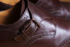 Abroche el detalle de un par de zapatos marrones clásicos de la abarca Foto de archivo libre de regalías