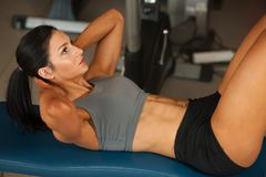 Abs подбрюшных мышц разминки женщины красивых детенышей подходящий в fitne стоковое изображение