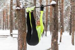 ABS adatto di addestramento della ragazza sollevando le gambe su una barra horisontal Allenamento della donna di forma fisica che Immagini Stock