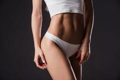 Abs av slanka muskulösa kvinnor som isoleras på vit Fotografering för Bildbyråer