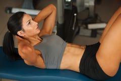 ABS convenable de muscles abdominaux de séance d'entraînement de femme de beaux jeunes dans le fitne image stock