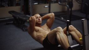Abs crunches on bench. Young athletic man doing abs crunches on bench. Shallow depth of field. Loop
