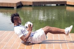 Abs exercise. Afro-American man doing exercises for his abs with soccer ball Royalty Free Stock Image