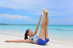 Abs exercise fitness woman - toe touch crunches. Fitness woman training abs with toe touch crunches. Young adult Asian girl doing abdominal exercises Stock Images