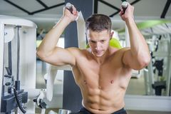 Abs exercise on a machine. Young bodybuilder working out in gym, doing ab exercise crunches using a machine Royalty Free Stock Photos