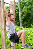 Abs exercise outside fitness station park. Man training core muscles with leg lift on vertical ladder rack on an outdoors gym on beach Stock Photo