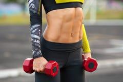 Abs för konditionkvinnavisning och lägenhetbuk Muskulös flicka med dumbbels, formad buk- slank midja fotografering för bildbyråer