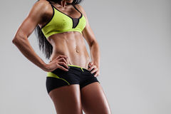 Abs muscles fitness. Brutal athletic woman showing abs muscles on gray background Royalty Free Stock Photos
