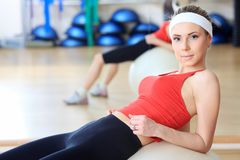 Abs training. Young sporty woman in the gym centre royalty free stock photo