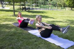 Abdominal exercise.Girls are doing stomach exercises. Abs workout in the park.Two girls are doing exercises for the stomach royalty free stock image