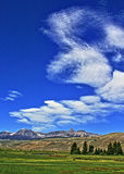 Absaroka Mountain Range under summer cirrus and lenticular clouds near Dubois Wyoming Stock Photo