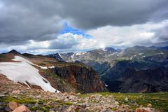 Absaroka Mountains in Beartooth Pass. Dark clouds roll in covering blue sky over Beartooth Pass, and the Absaroka Mountains in Wyoming.  Snow runs down cliff Stock Photo