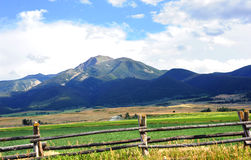 Absaroka Mountains Loom Over Farm. Distant Absaroka Mountains serve as backdrop for this farm surrounded by rustic wooden fence.  Water irrigation system works Royalty Free Stock Image