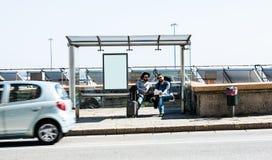 Abschüssige Bushaltestelle - zwei Freunde sind, wütend werden wartend und wegen der Verzögerung Stockfotos