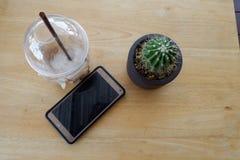 Abschaltzeit, Kaffeemobiltelefon auf hölzerner Tabelle Stockbild