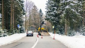 Abschleppwagen, der an deutscher Straße während des Winterfrostschnees arbeitet Lizenzfreie Stockbilder