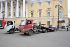 Abschleppwagen nimmt Autos unter Aufsicht der Polizei Stockbild