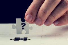 Abschließendes Puzzlespielstück mit einem Fragezeichen Stockbild