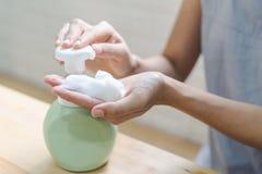 Abschluss der Frauenhand nehmen saubereren Schaum auf stockfotos