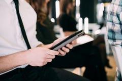 Abschluss des jungen Mannes mit Tablette bilden Mitteilung bei der Darstellung oder bei der Sitzung des Büroteams teamwork Lizenzfreies Stockbild