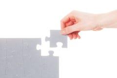 Abschluss des letzten Stückes des Puzzlen lösung Stockbild