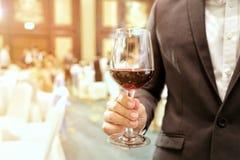 Abschluss des tragenden Anzugs des Geschäftsmannes, der ein Glas Wein in der Firmenpartei mit gelbem Licht des Strahls im Hinterg Lizenzfreie Stockfotografie