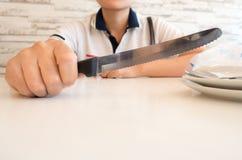 Abschluss einer Frau in der zufälligen Kleidung halten ein Messer hoch Stockfotografie