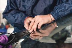Abschluss herauf Autoglasurarbeitskraftfestlegung und -reparatur einer Windschutzscheibe oder der Windschutzscheibe eines Autos a stockfoto