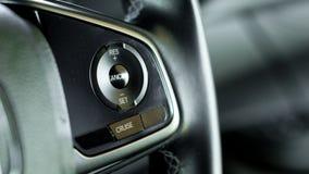 Abschluss herauf AutoReisegeschwindigkeitskontrolle auf Autolenkrad mit unscharfem c stockfotos
