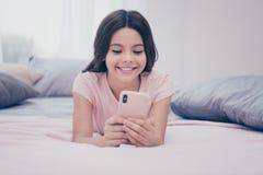 Abschluss herauf das Foto nett schön sie ihr kleines Mädchen, das unten wohnliches Telefon-Handarm-Leser Leineninstagram Sonntags stockbild