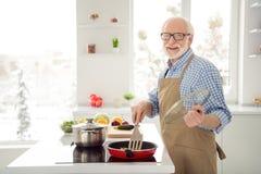 Abschluss herauf das Fotograu behaart er sein er Großvaterkoch, der kochende beschäftigte köstliche Tellerprozessfreizeit brät si lizenzfreies stockbild