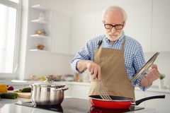 Abschluss herauf das Fotograu behaart er sein er Großvaterkochteller, der den kochenden beschäftigten köstlichen Kocher aufmerksa lizenzfreies stockbild