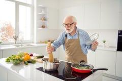Abschluss herauf das Fotograu, das genießt er behaart ist, sein er der Großvaterkoch, der kochenden beschäftigten köstlichen Tell stockfoto