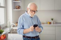 Abschluss herauf das Porträtgrau behaart er sein er Großvater starke Telefon-Lesernachrichten des Handarm-Telefons intelligente A stockfotografie