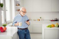 Abschluss herauf das Porträtgrau, das sieht er behaart ist, sein er Großvaterheißgetränk-Handarmuhr Telefon-Leserabnutzung des Bl stockfoto