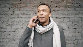 Abschluss herauf den afroen-amerikanisch Mann, der am Telefon spricht H?bscher Afroamerikanerkerl in einem Mantel und in einem Sc stock footage