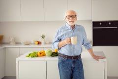 Abschluss herauf den Porträtbeifall grau behaart er sein er stolzes Küchenmageres des Großvaters, das Tabellenheißgetränk-Handarm lizenzfreie stockfotografie