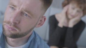 Abschluss herauf den unglücklichen jungen Mann des Gesichtes, der weg im Vordergrund schaut Die unscharfe Zahl reifer Dame ihren  stock video