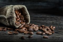 Abschluss herauf die Ansichtbohnen des Kaffees zerstreut vom Sack lizenzfreie stockfotos