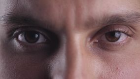 Abschluss herauf die braunen Augen des jungen Mannes untersuchend Kameraobjektiv Makro stock video