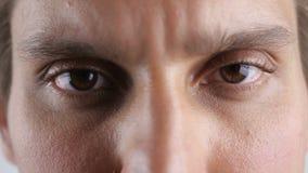 Abschluss herauf die braunen Augen des jungen Mannes untersuchend Kameraobjektiv Makro stock video footage
