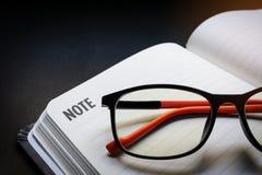 Abschluss herauf die Gläser gelegt auf offene Leerzeile Notizbuch mit schwarzem Schreibtischhintergrund in drastischen beleuchten lizenzfreie stockbilder
