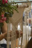 Abschluss herauf die Hände, die Makrameetapisserie mit beige Faden spinnen stockfoto