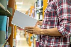 Abschluss herauf die Handstudentenmänner, die Buch für das Ablesen in der Bibliothek finden getrennte alte B?cher lizenzfreies stockfoto
