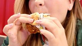 Abschluss herauf die junge Frau, die leckeren Hühnerburger im Schnellimbisscafé isst stockfotografie