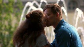Abschluss herauf die Paare, die auf dem Hintergrund des Brunnens küssen stock video footage