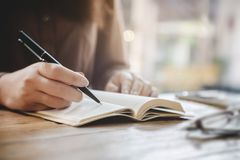 Abschluss herauf die weiblichen Hände, die auf Notizbuch am Café schreiben lizenzfreie stockfotografie
