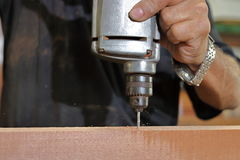 Abschluss herauf elektrische Bohrmaschine wird an hölzernem Brett durch Hände des älteren Tischlers in der Zimmereiwerkstatt gear Lizenzfreie Stockbilder