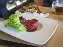 Abschluss herauf frisches Tatarbeefsteak mit Kopfsalat verlässt auf weißer Platte, lizenzfreie stockbilder